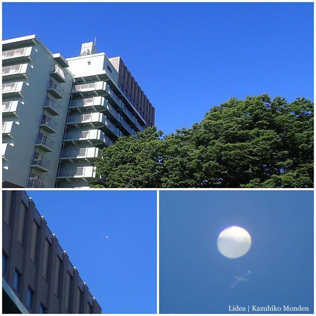 青葉山の上?あたりに何か白い球体が浮かんでる。望遠で見てみたら十字のフレームに小さなプロペラがいくつも付いてた。観測気球…?